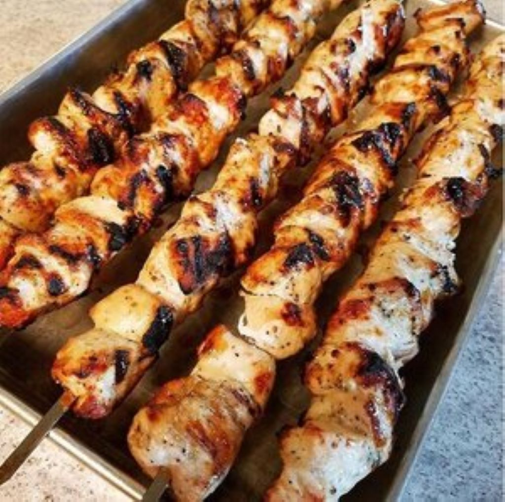 Grilled chicken skewers resting on metal pan