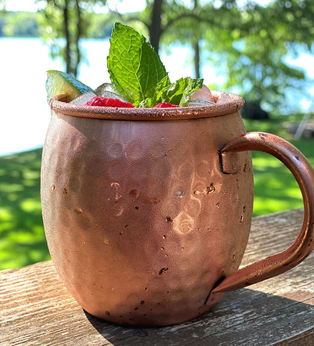 Raspberry Moscow mule in copper mug with summer background