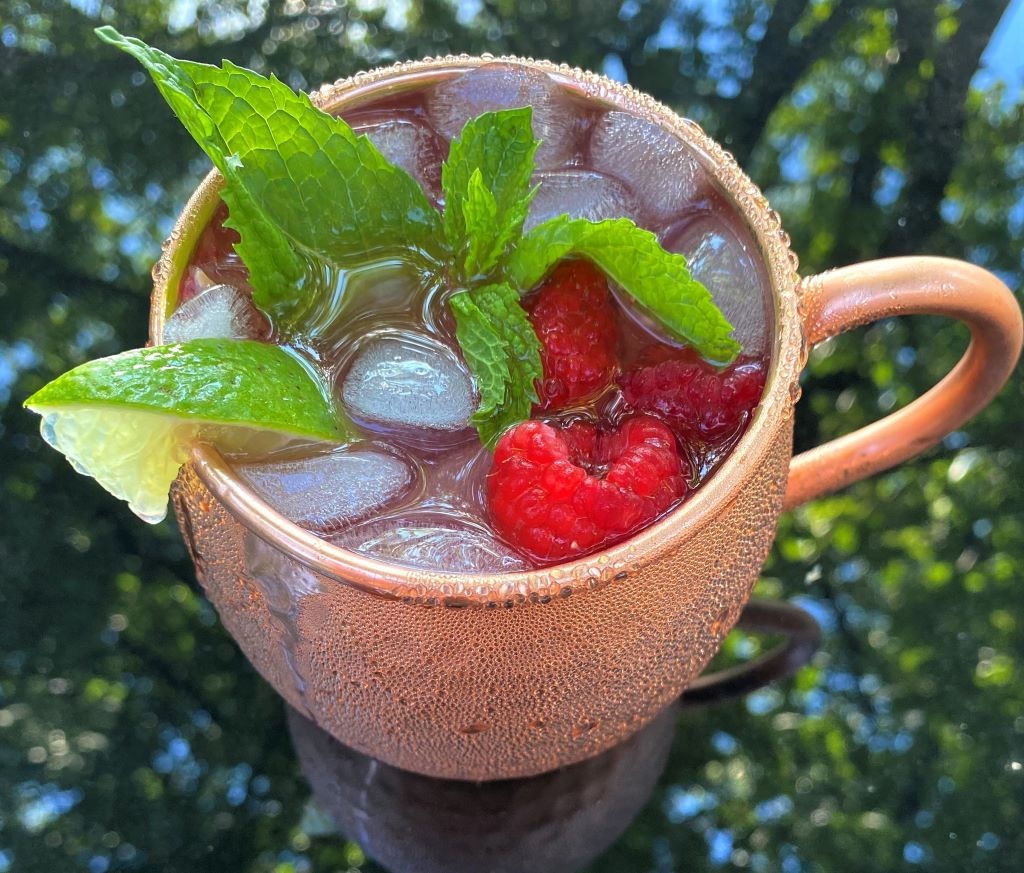 Raspberry Moscow mule in a copper mug with mint and lime