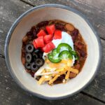 Low sodium chili with diced tomatoes, black olives, and sour cream in ceramic bowl