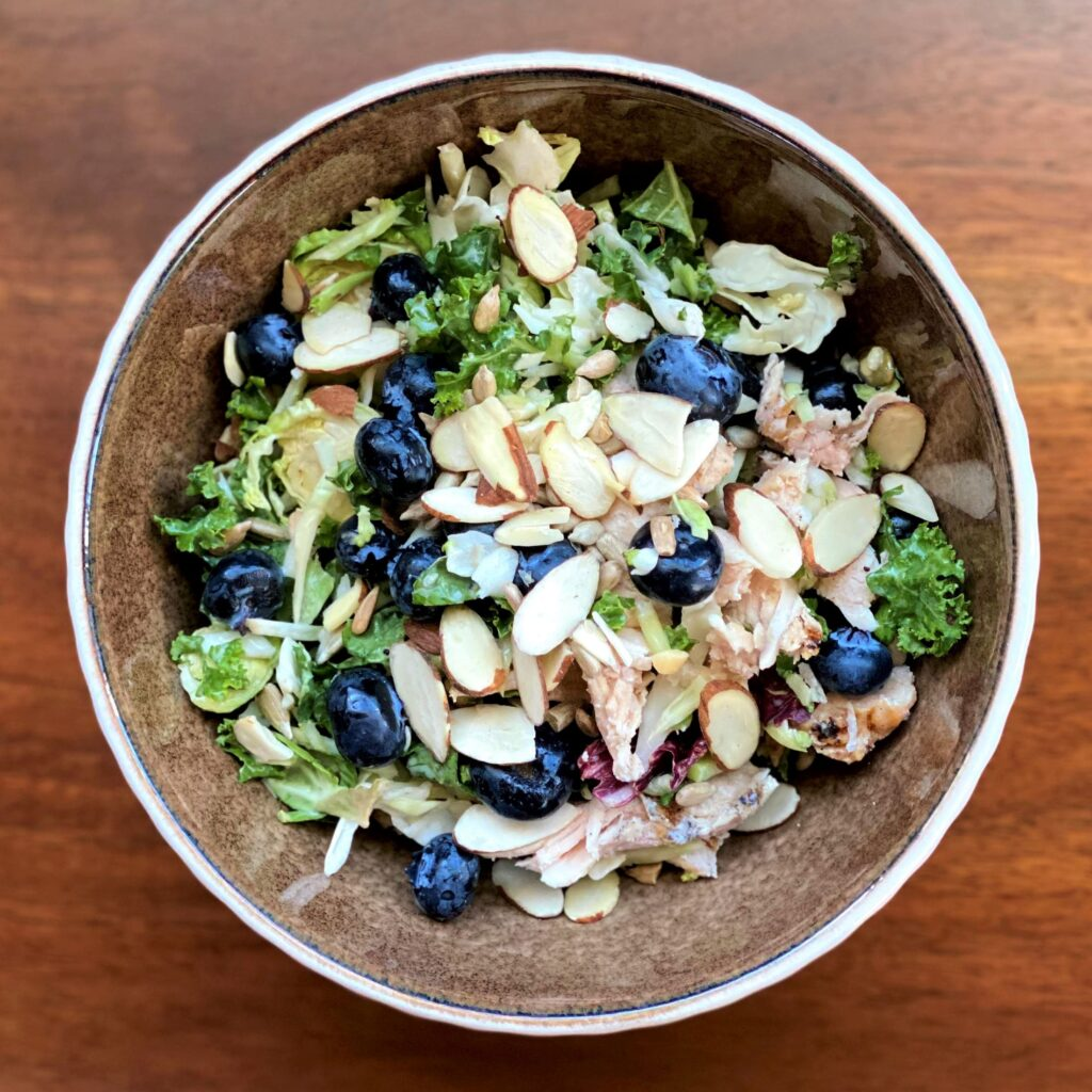 Sweet kale salad with blueberries, chicken, and sliced almonds