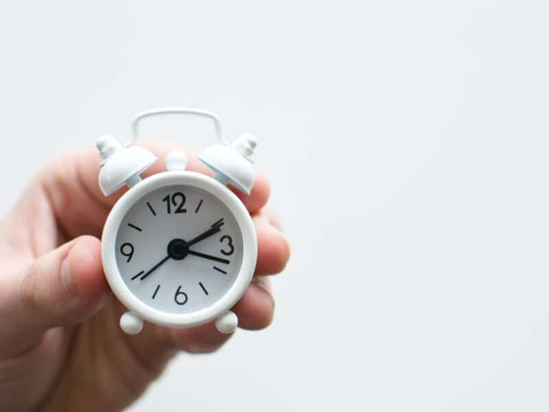 Hand holding a white clock with white background